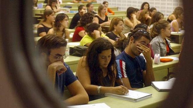 Unos alumnos atienden en una clase de Universidad de Valencia, al otro lado de la puerta.