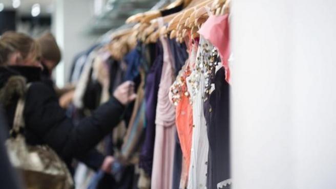 Unas mujeres, mirando ropa en una tienda.
