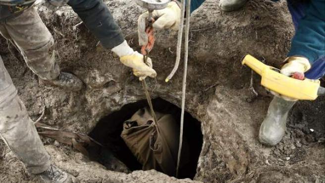 Miembros de la sociedad Arazandi suben una bolsa con los restos de uno de los diez cadáveres que han sido hallados a más de diez metros de profundidad de la sima El Raso, en la sierra de Urbasa (Navarra).