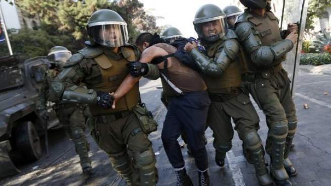 Fuerzas especiales de carabineros detienen a un manifestante en disturbios en Santiago de Chile.