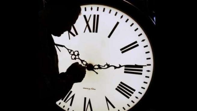 Un hombre cambia la hora en un reloj.