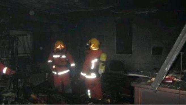 Bomberos en el interior de la vivienda afectada por el fuego en Torrent