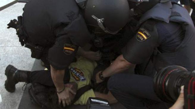 Varios agentes intentan inmovilizar a un detenido.