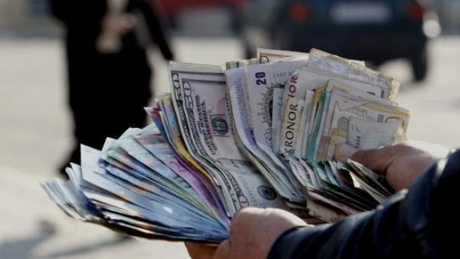 Un hombre ofrece cambio de divisas mientras muestra un abanico de billetes.