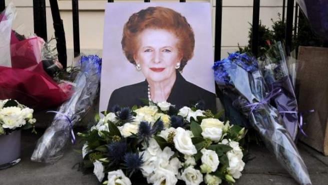 Varias personas depositan flores y artículos relacionados con Margaret Thatcher en la puerta de su casa.