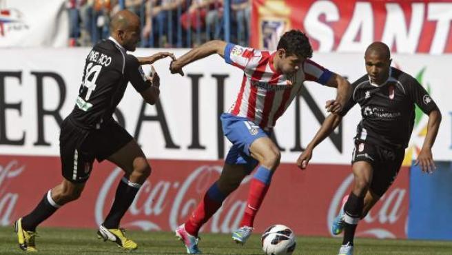 Diego Costa controla el balón ante dos defensores del Granada.