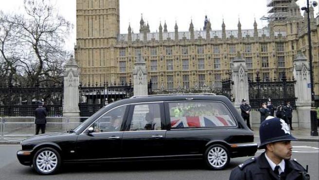 El coche fúnebre con los restos mortales de la ex primera ministra británica Margaret Thatcher pasa junto al Big Ben y las Casas del Parlamento de Londres en Reino Unido. El ataúd de Thatcher, cubierto con la bandera británica y un ramo de rosas blancas, permaneció toda la noche en una capilla del Palacio de Westminster, sede del Parlamento.