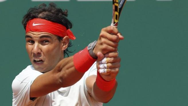 El tenista español Rafael Nadal devuelve una bola.