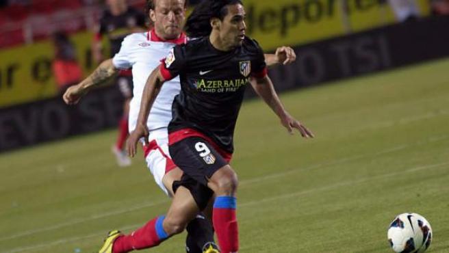 El croata del Sevilla Ivan Rakitic persigue a Radamel Falcao, delantero centro colombiano del Atlético de Madrid.
