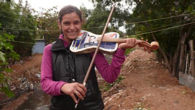 Tania, violinista de la Orquesta de Instrumentos Reciclados de Cateura, con uno de los instrumentos hechos a partir de residuos
