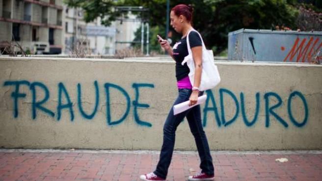 Una mujer camina frente a una pared que tiene mensajes de fraude electoral el 22 de abril de 2013, en Caracas (Venezuela).