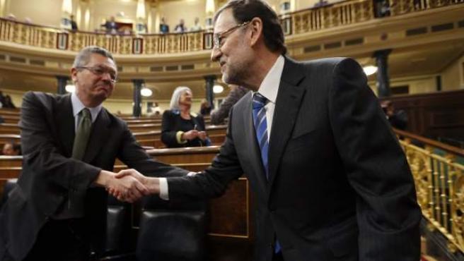 Rajoy (d), estrecha la mano del ministro de Justicia, Alberto Ruiz Gallardón (i).