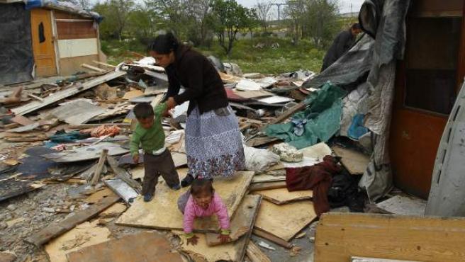 Una madre y sus hijos sobre los restos de una de las viviendas derruídas por el Ayuntamiento de Madrid en el poblado de El Gallinero.
