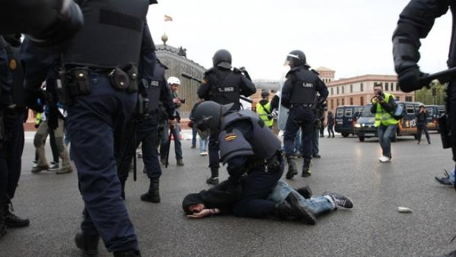 La policía detiene a un joven durante la protesta del 25-A cerca de la estación de Atocha