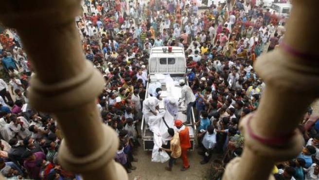 Familiares de los trabajadores desaparecidos en el derrumbe de una fábrica textil en Bangladesh se agolpan en torno a una furgoneta para intentar identificar a sus conocidos.