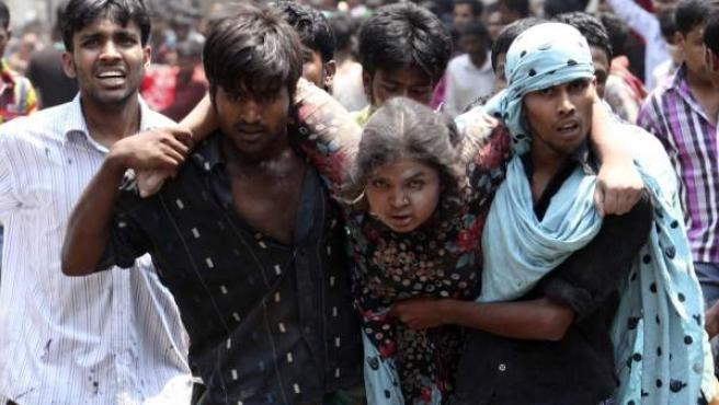 Un grupo de personas rescata a una trabajadora herida tras el colapso del edificio de ocho plantas Rana Plaza, en Savar, Dacca, Bangladesh. Al menos 70 personas murieron y unas 600 resultaron heridas al derrumbarse un edificio en las afueras de Dacca, capital de Bangladesh.