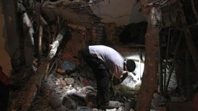 Un voluntario de las tareas de rescate en el derrumbe de un edificio de talleres textiles en Bangladesh busca con su linterna a posibles víctimas atrapadas entre los escombros.
