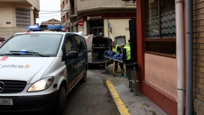 Técnicos de la comitiva judicial sacan el cuerpo del hombre asesinado en un bar de Alcarràs (Lleida).