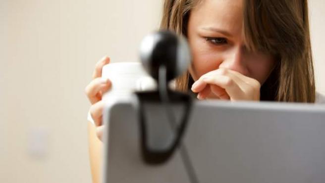 Recreación de una mujer observada por la webcam de su portátil.