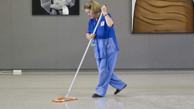 Una señora de la limpieza realiza su tarea en un museo.