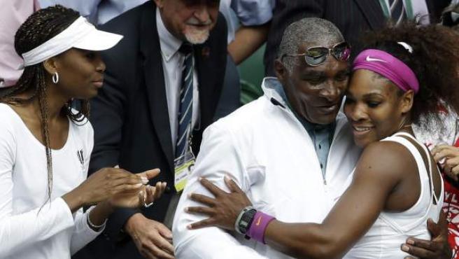 Serena Williams abraza a su padre, Richard Williams, bajo la mirada de su hermana Venus (izda.)