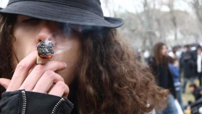 Un joven aspira unas caladas de un porro de cannabis.