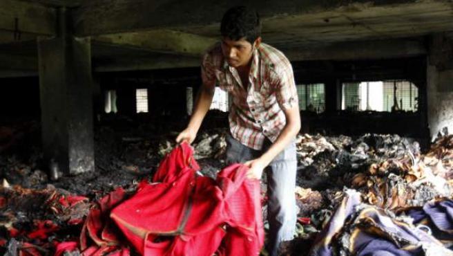 Un trabajador observa un montón de chaquetas en la fábrica donde se ha producido un incendio en Daca (Bangladés) este jueves.