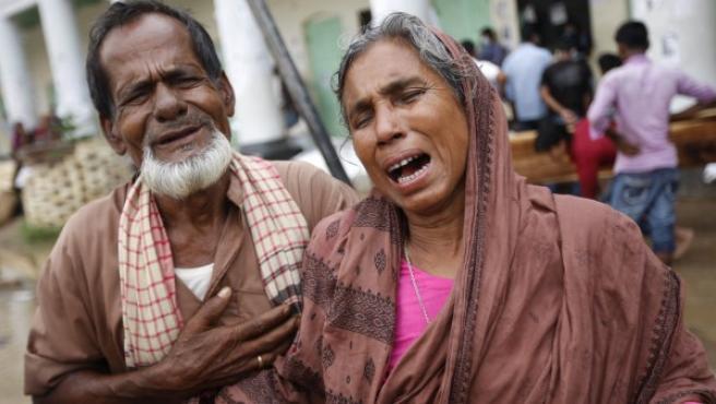 Una pareja llora desconsolada tras reconocer el cadáver de su hijo en el complejo textil derrumbado en Bangladesh.