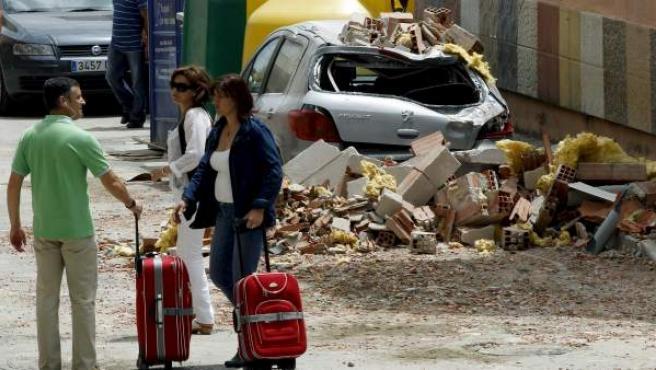Unas personas con maletas en una calle de Lorca llena de escombros y daños materiales provocados por el terremoto de 5,2 grados.