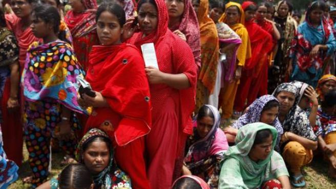 Trabajadores del edificio derrumbado en Bangladesh, esperando para cobrar sus salarios.