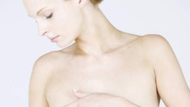 Una mujer se explora los senos.