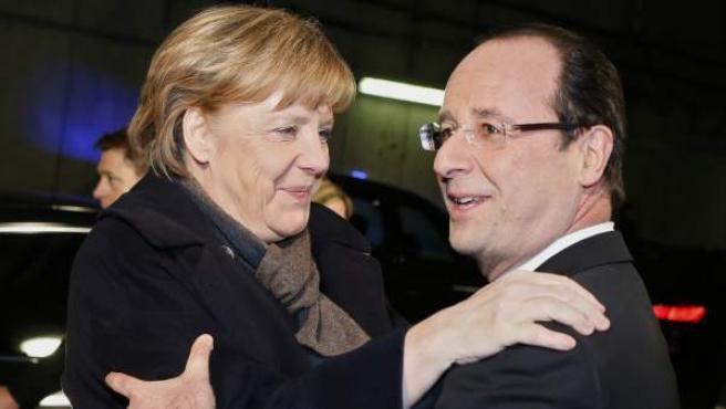 El presidente francés Francois Hollande y la canciller Angela Merkel se abrazan durante un encuentro deportivo.