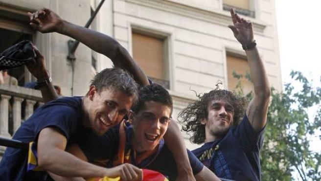 Los jugadores del FC Barcelona, Marc Muniesa (i), Marc Bartra (c) y Carles Puyol, en el autobús de la fiesta del Barça por ganar la Liga.