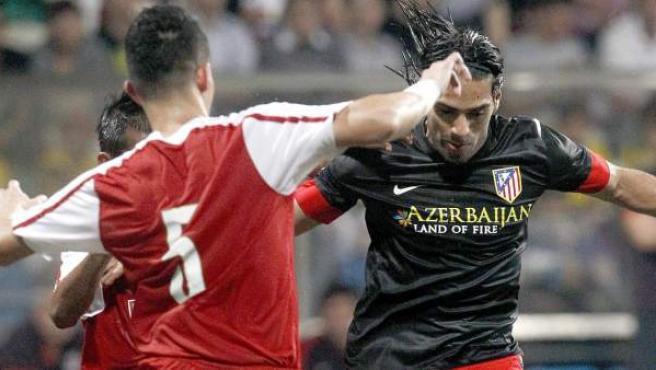 El colombiano Radamel Falcao conduce el balón presionado por varios rivales durante un amistoso disputado por el Atlético de Madrid en Singapur.