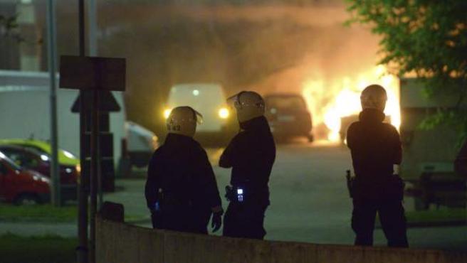 Miembros de la policía observan un vehículo en llamas durante los disturbios ocurridos en Estocolmo.