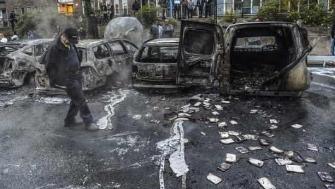Varios coches calcinados tras ser incendiados por algunos de los participantes que se llevan produciendo varios días en Suecia.