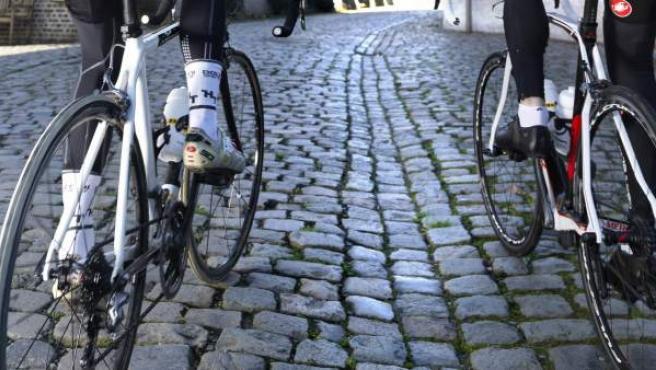 Dos ciclistas las pendientes empedradas de uno de los repechos que jalonan el recorrido del Tour de Flandes.