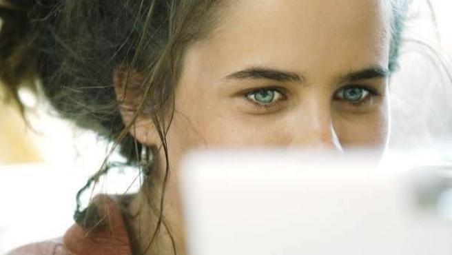 Una joven mira su ordenador.