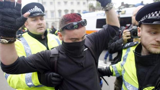 Agentes de la policía británica detienen a un manifestante, simpatizante de grupos antifascistas, tras los choques entre ultraderechistas y antirracistas en Londres.