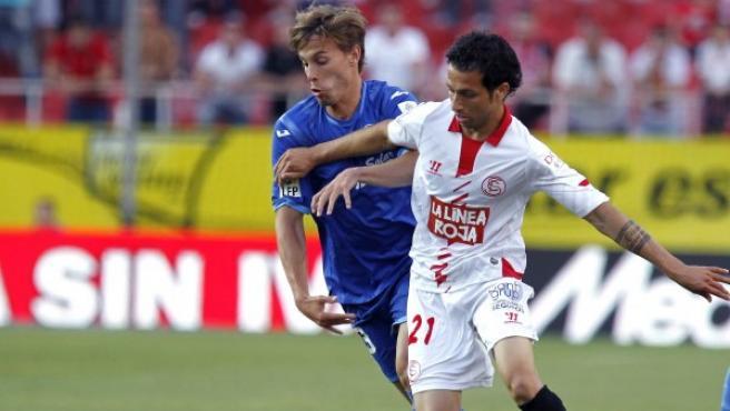 El defensa brasileño del Sevilla Cicinho (d) disputa un balón con Canales, del Valencia.