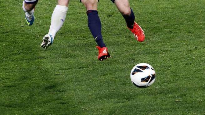 Dos jugadores disputan un balón durante un encuentro de fútbol.