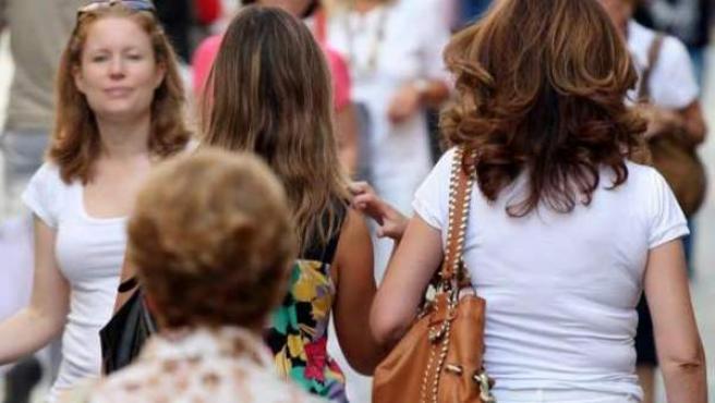 Varias mujeres pasean por una calle.