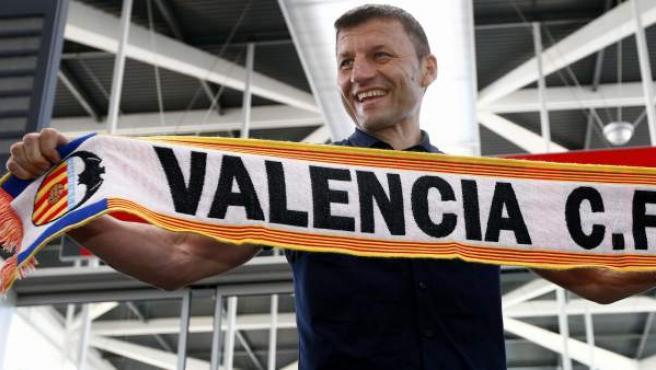 El entrenador serbio Miroslav Djukic posa con una bufanda del Valencia CF a su llegada a Valencia para cerrar los últimos detalles de su fichaje por la entidad de Mestalla.