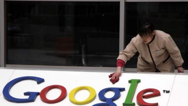 Una empleada limpia un logotipo de Google en su sede china.