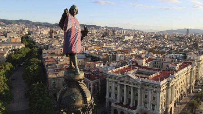 La estatua de Colón, situada al final de las Ramblas barcelonesas, luce por motivos publicitarios una réplica de la nueva camiseta del FC Barcelona, que recupera las tradicionales rayas verticales azulgranas.