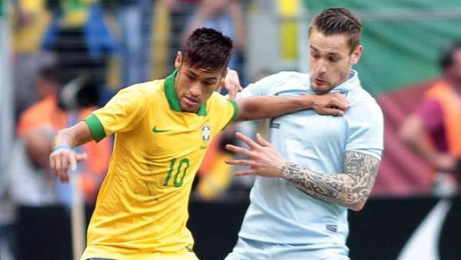 Neymar, de Brasil, lucha un balón con Debuchy, de Francia.
