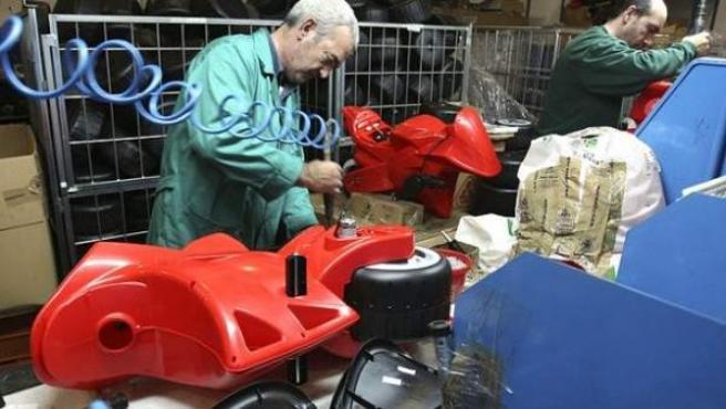Dos trabajadores de una cadena de montaje de juguetes en Ibi, Alicante.