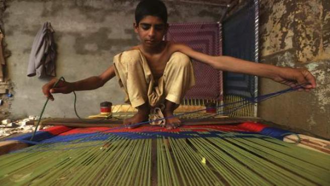 Un niño paquistaní prepara una cama hecha a mano en Peshawar (Pakistán).