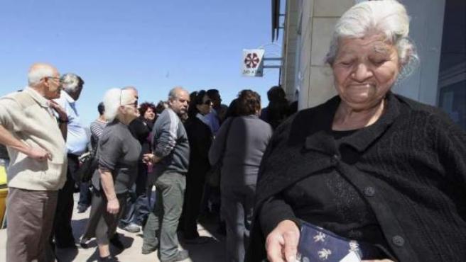 Chipriotas aguardan la apertura de una sucursal del Banco Laiki, en Nicosia (Chipre).