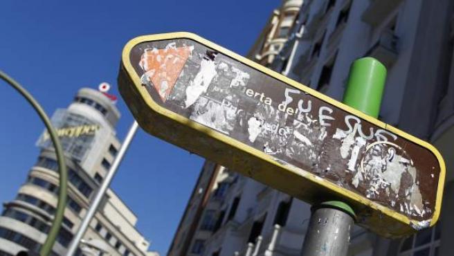 Una señal turística en Gran Vía, indicando la dirección de la Puerta del Sol, con gran parte de su leyenda tapada por pegatinas y grafitis.